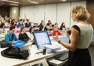 A professor speaking to students in a large classroom.