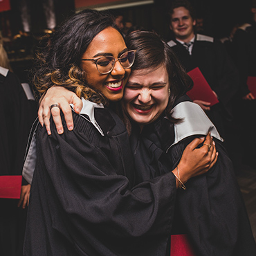 Two female graduates hug with smiles of joy and happiness.