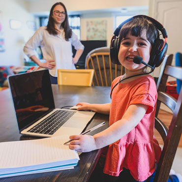 A young child wearing a headset sits in front of a laptop as her mother watches her in the background.