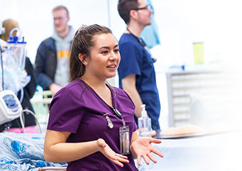 A female nursing student in hospital scrubs welcomes participants to an open house, a male nursing student stands in the background.