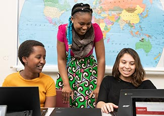 Teacher and two students in classroom with laptops.