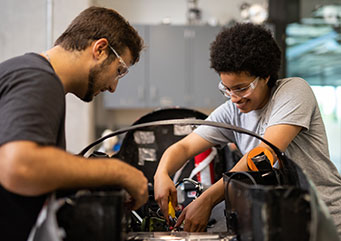 Two engineering students constructing a fuel-efficient vehicle.