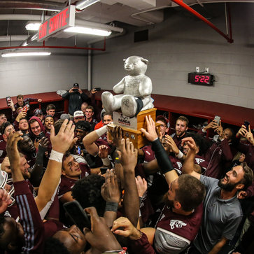 The Gee-Gees celebrating in the locker room with the Panda Game trophy Pedro.