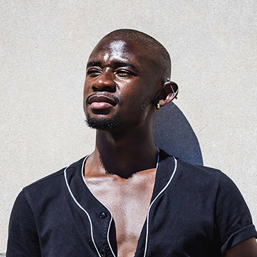 Sekalala Seguya leans against concrete wall with sunlight on his face.