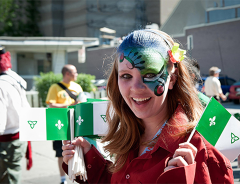 A smiling female student with a celebratory face painting holds