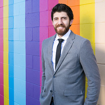 Tareq Hadhad standing in front of a colourful wall.