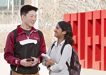 Two smiling students carrying books chat on campus.