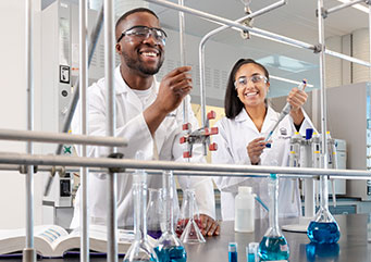 Two smiling science students, one male and one female, wearing lab coats and safety glasses handle beakers filled with liquids in a lab.