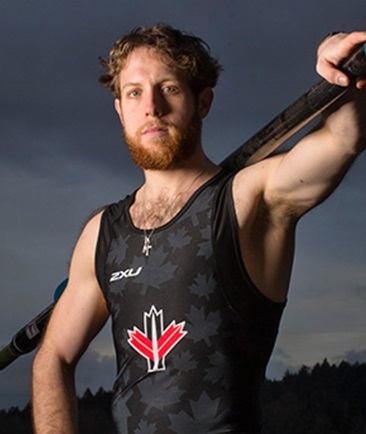 Andrew Todd wearing a sleeveless Lycra shirt with an oar slung across his shoulder