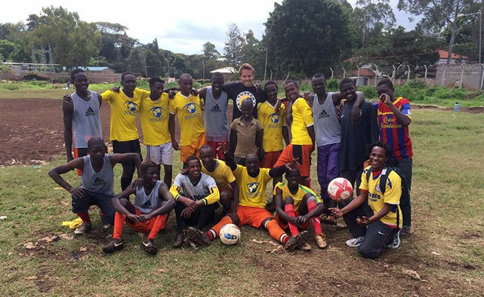 Dylan Corbett standing with a group of 18 youths dressed in soccer uniforms.