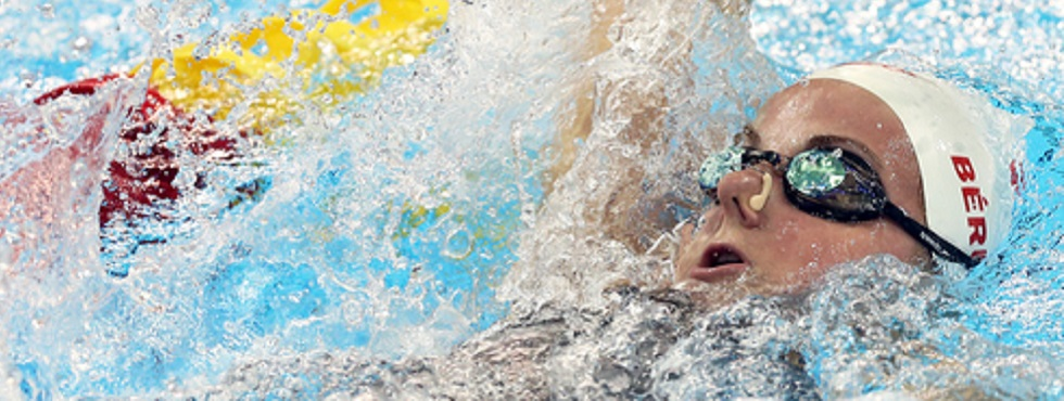 Camille Bérubé swims backstroke in churning water.