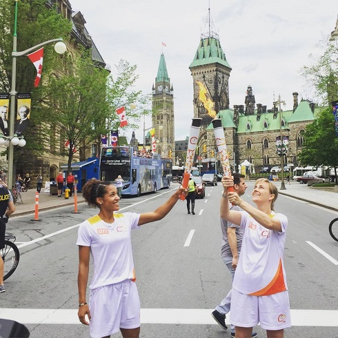 Karelle Edwards lève le flambeau des Jeux Panam vers un second flambeau tenu par une autre porteuse. La Tour de la Paix du Parlement canadien et en arrière-plan.