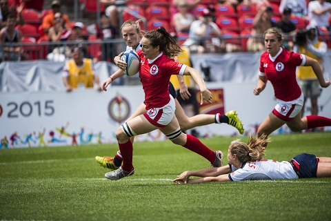 Natasha Watcham-Roy courre avec un ballon de rugby. Une coéquipière est à ses côtés alors qu'une joueuse de l'équipe adverse est au sol derrière elle.
