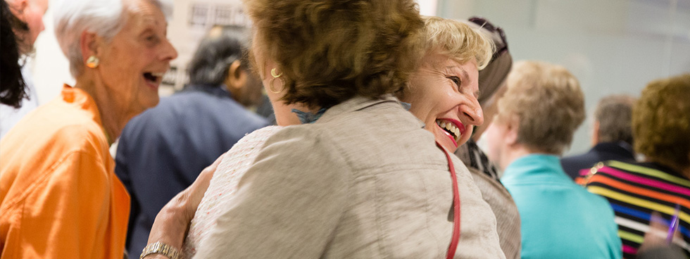 In a crowded room, two women hug enthusiastically and with joy.