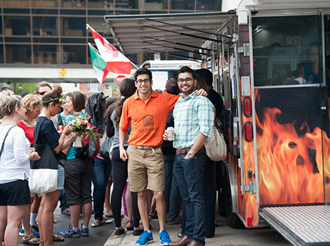 "Two men in their 20s, one dressed in a bright orange polo-styled shirt with ""uOttawa"" emblazoned on the front, pose for the camera. They stand beside a food truck, and a group of people are tightly crowded behind them waiting for service."