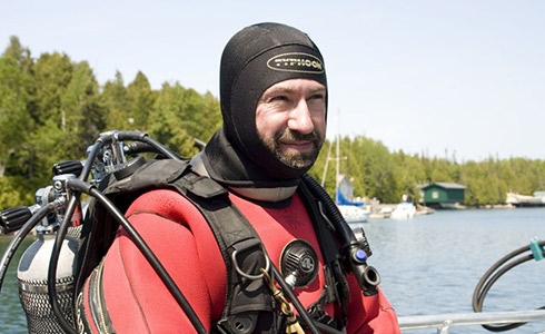 A man dressed in a red and black hooded wet suit sits on a boat. He's wearing scuba equipment, including tanks on his back.