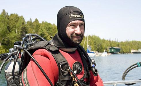 Un homme vêtu d'une combinaison isothermique rouge et noire est assis sur une embarcation. Il porte un équipement de plongée et deux bonbonnes dans le dos.