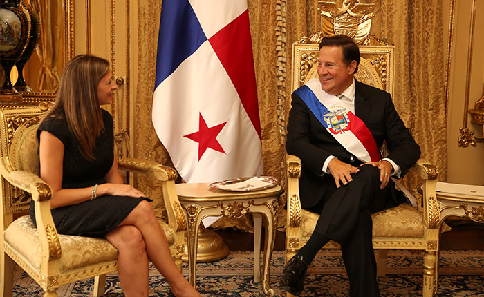 Karine Asselin and Panamanian president Juan Carlos Varela sit on gilded chairs next to the flag of Panama.