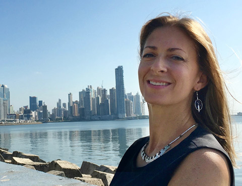Karine Asselin smiles next to a bay with skyscrapers and palm trees in the background.