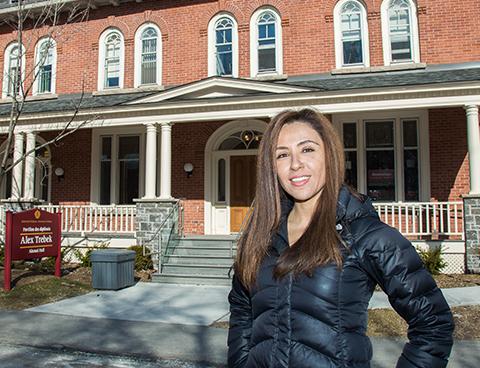 Une femme sourit, debout près du Pavillon des diplômés Alex-Trebek sur le campus de l'Université d'Ottawa.