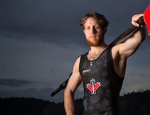 Andrew Todd wearing a sleeveless Lycra shirt with an oar slung across his shoulder.