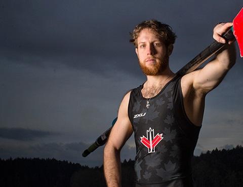 Andrew Todd porte un maillot d'entrainement en Lycra sans manches et tient un aviron sur son épaule.