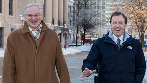 Deux hommes souriants, vêtus de manteaux d'hiver, marchent à l'extérieur sur un trottoir bordé de neige.