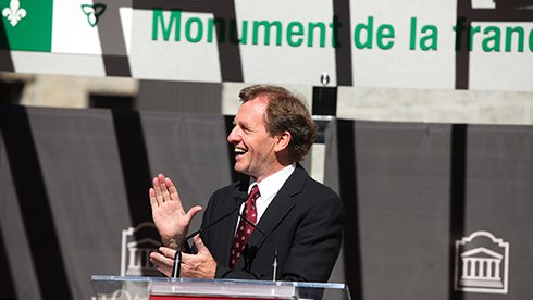 Allan Rock stands at a uOttawa podium, clapping his hands, with a sign that reads Monument de la francophonie in the background