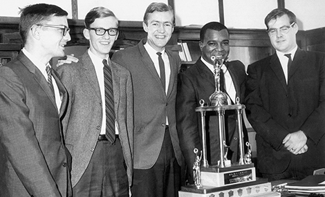 Black and white photo from the 1960s of five men standing around a trophy.
