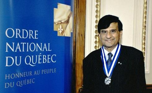 Ashok Vijh à côté d'un panneau indiquant « Ordre national du Québec »