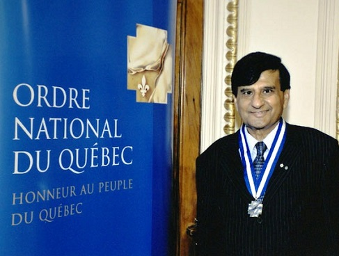 "Ashok Vijh stands beside sign that reads ""Ordre national du Québec"""