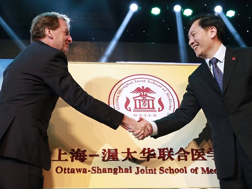 Deux hommes se serrant la main en face d'un emblème de L'École conjointe de médécine Ottawa-Shanghai.