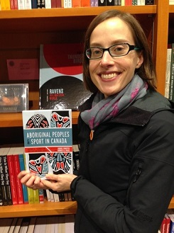A woman, standing in front of a bookshelf, holds a book titled Aboriginal Peoples and Sport in Canada.