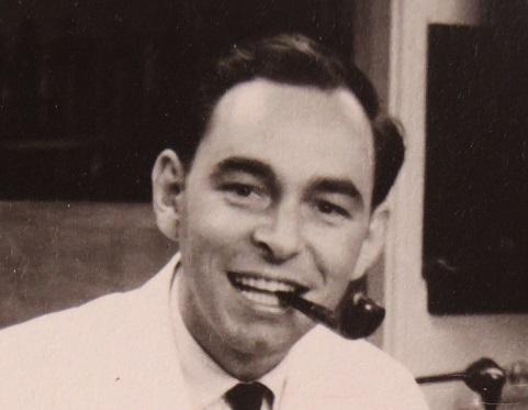 Photo en noir et blanc du professeur Hans Baer arborant la pipe et un sarreau blanc.
