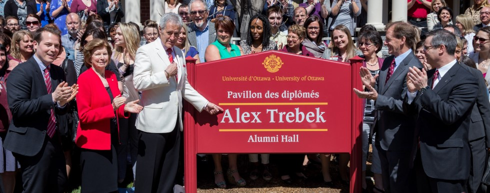 Hundreds of uOttawa staff stand in front of the Alex Trebek Alumni Hall.