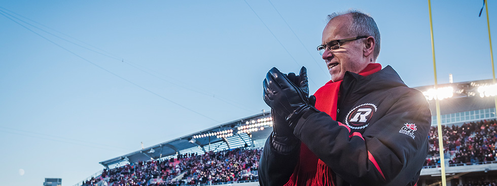 A man wearing a Redblacks jacket smiles and claps his hands. Stadium stands seen in the background are filled with fans.