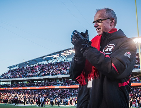 Bernie Ashe, wearing a Redblacks jacket, scarf and gloves, smiles and claps his hands, with a crowded stadium and playing field in the background.