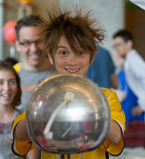 A boy's hair stands on end, probably due to electricity from the metal ball he is touching.