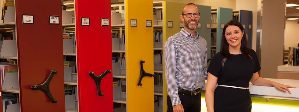 David Smith and Karen Bouchard stand, smiling, with shelves holding books and magazines in the background.