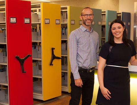 David Smith et Karen Bouchard se tiennent debout, souriants, à l'intérieur d'une bibliothèque aux étagères garnies.