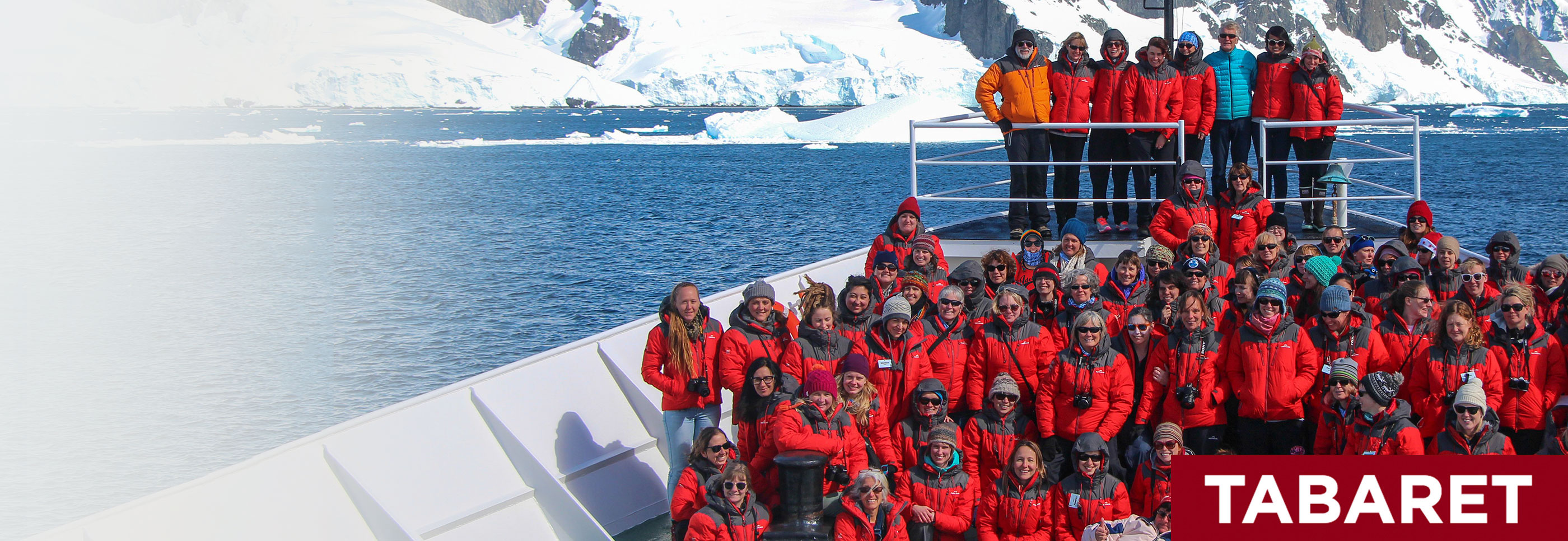: Several dozen people, mostly women, wearing cold-weather gear on a ship deck, with snow-covered cliffs in the background.