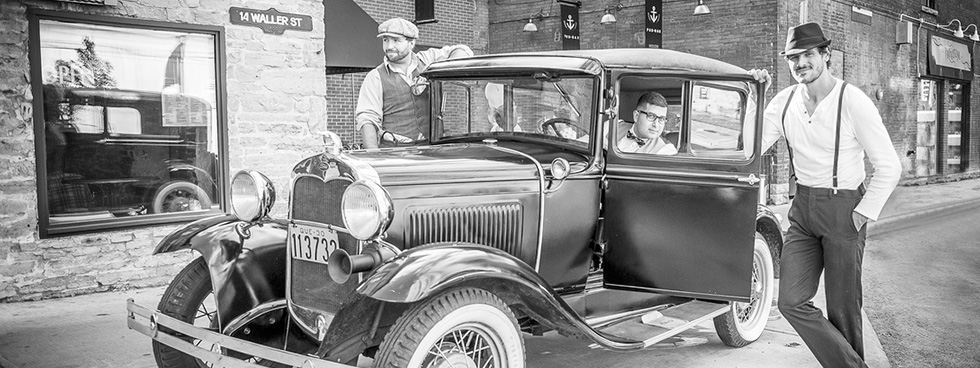 A black and white picture of three men dressed in early 1900s style near a vintage car parked on Waller Street.