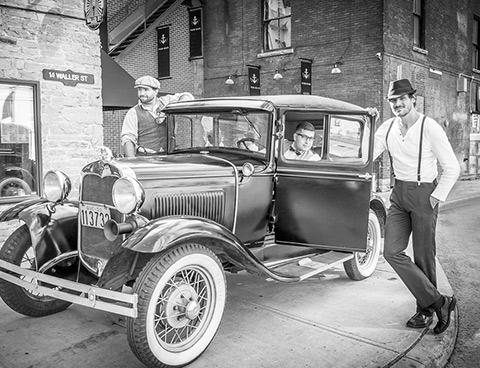 Une image en noir et blanc montre trois hommes, habillés à la façon du début du 20e siècle, près d'une voiture d'époque stationnée rue Waller.