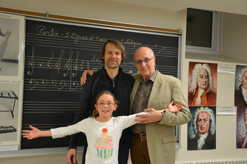 A girl, Charlotte, sings with her father, Alain, and grandfather, Ubald as part of the Francophonia choir.