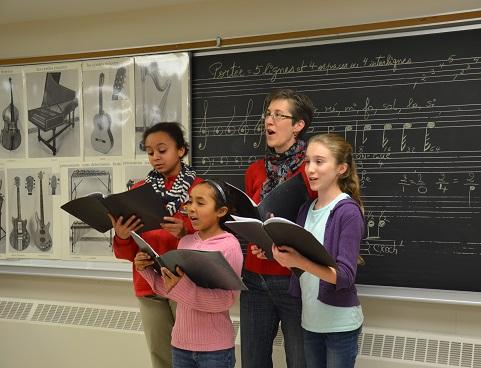 Marie Josée Vignola, professeure à la Faculté d'éducation de l'Université d'Ottawa, accompagnée de trois jeunes choristes.