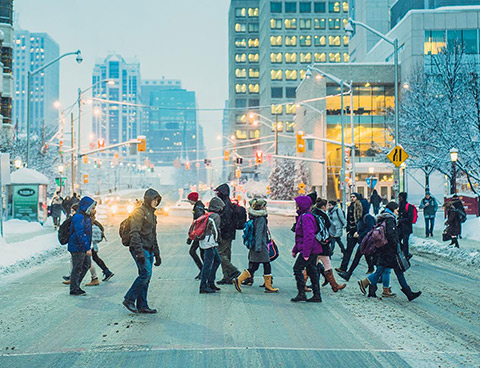 Winter scene showing many students crossing a busy street on campus. Downtown Ottawa in the background.