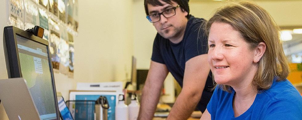 Renée Black est assise devant un écran d'ordinateur portatif, alors que son collègue Carey Hoffman regarde par-dessus son épaule.