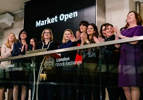 A group of women smiling and applauding as the London Stock Exchange opens for the day.
