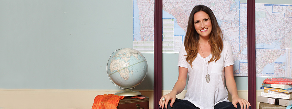 A smiling young woman is seated on the ground, surrounded by books, a globe and a map of the world.