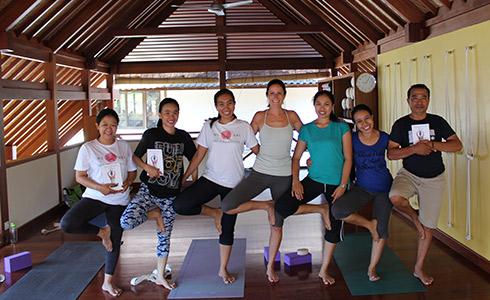Des personnes se tiennent debout dans une position traditionnelle de yoga, un livre dans les mains.